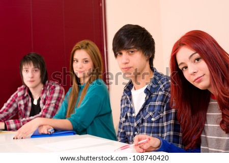Teenage students in classroom looking at camera