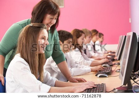 Teenage Students In IT Class Using Computers In Classroom With Tutor