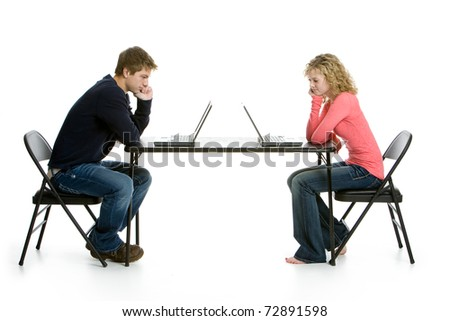 Teenage students using laptops on white background in studio