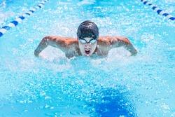 Teenage swimmer swimming butterfly stroke in a race
