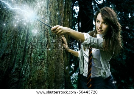 Teenage wizard girl with magic wand casting spells in a enchanted fantasy forest