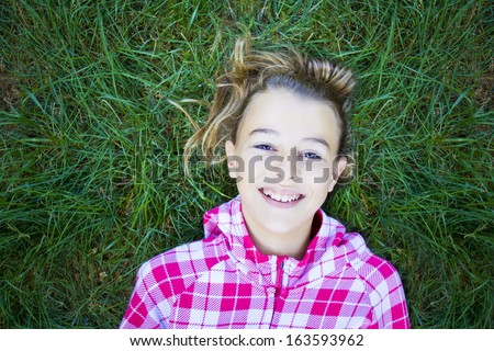 Teenage woman with checked print white hoodie lying back on green grass, laughing and looking at the camera. Candid shot, real people