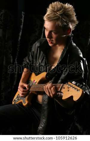 Teenage young man playing an electric guitar wearing a leather jacket on a dark background looking away