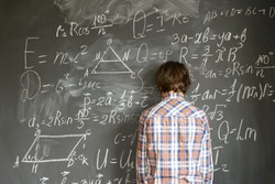 Teenageer Boy having trouble with complicated math formulas on black board