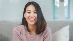 Teenager Asian woman feeling happy smiling and looking to camera while relax in living room at home.