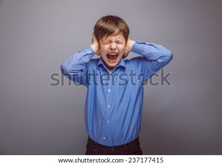 teenager boy covering his ears screaming hands on a gray background