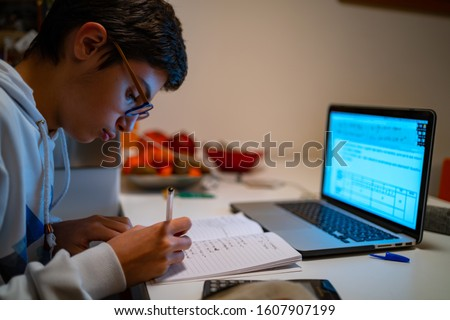 Teenager boy doing homework at home with laptop and writing notes.