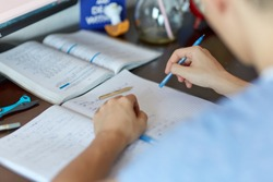 Teenager boy doing homework on his desk at home