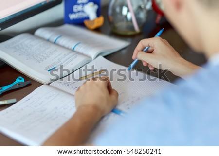 teenager boy doing homework on...