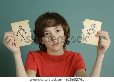 teenager boy hold mom and dad drawing in two torn paper pieces as a symbol of divorce close up sad portrait