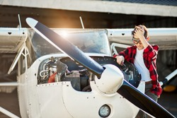 teenager boy in aviator glasses stands near opened light airplane motor cabinet, holds screwdriver, tries to fix failure, looks puzzled and stressed, hangar building on background.