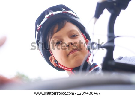 Teenager boy in protective helmet sitting on his bicycle in park on summer day and looking into the camera looking down. #1289438467