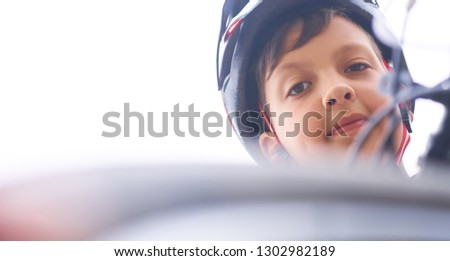 Teenager boy in protective helmet sitting on his bicycle in park on summer day and looking into the camera looking down. #1302982189