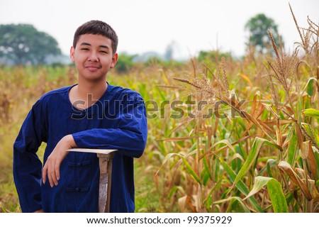 Teenager boy in thailand's farmer dress at corn field - stock photo