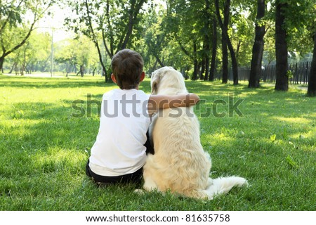 Teenager boy in the park with a golden retriever dog