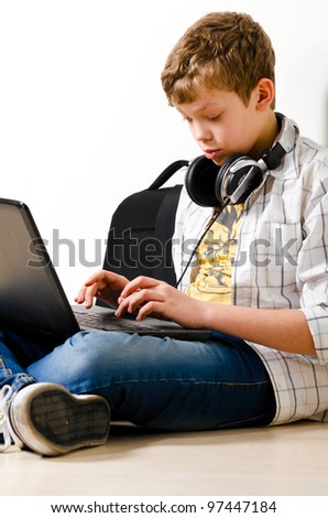 teenager boy is sitting with laptop at school