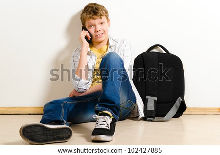 teenager boy is talking phone at school
