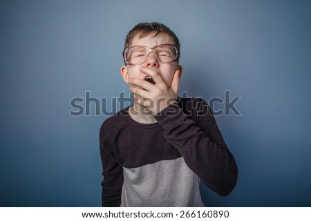 teenager boy of European appearance with glasses covers her mouth yawns on a gray background, drowsiness, fatigue