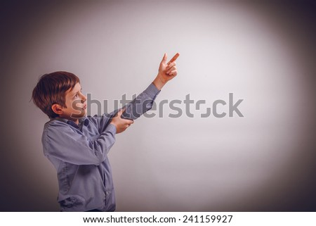 teenager boy of 10 years of European appearance shows up on a gray background cross process