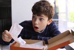 teenager boy shocked expression after see bill for pizza in fast food restaurant
