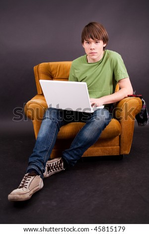 Teenager boy sit on an old armchair with a white laptop