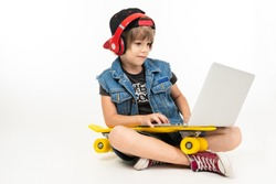 Teenager boy sits on floor in denim jacket and shorts. sneakers with yellow penny, red earphones and laptop isolated on white background