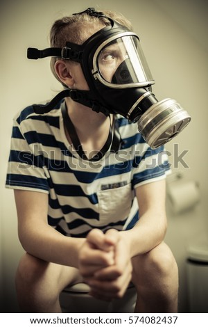 Teenager boy sitting on toilet seat with pants off wearing gas mask, looking away