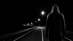 Teenager boy standing alone in the street at night, Black & White tone