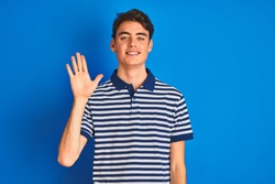 Teenager boy wearing casual t-shirt standing over blue isolated background Waiving saying hello happy and smiling, friendly welcome gesture
