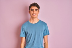 Teenager boy wearing casual t-shirt standing over blue isolated background with a happy and cool smile on face. Lucky person.