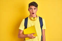 Teenager boy wearing headphones and backpack reading a book over isolated background scared in shock with a surprise face, afraid and excited with fear expression