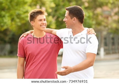 Teenager boy with father in park