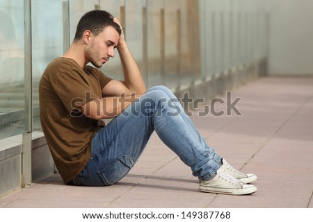Teenager Boy Worried Sitting On The Floor With A Hand On The Head