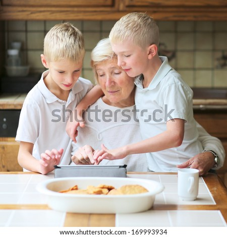 Teenager boys twin brothers teaching grandmother to play on tablet pc, enjoying time together, eating cookies and drinking coffee