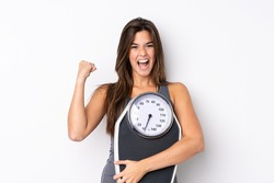 Teenager Brazilian girl holding a scale over isolated white background with weighing machine and doing victory gesture