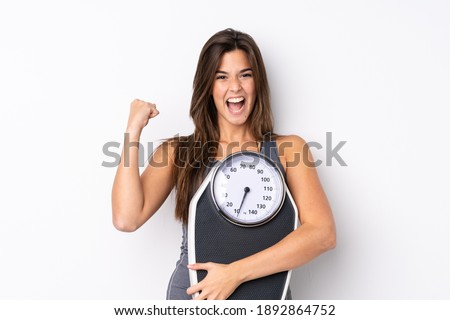 Teenager Brazilian girl holding a scale over isolated white background with weighing machine and doing victory gesture Photo stock ©