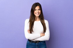 Teenager Brazilian girl over isolated purple background keeping the arms crossed in frontal position