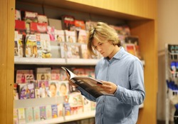 Teenager buying a magazin in a store