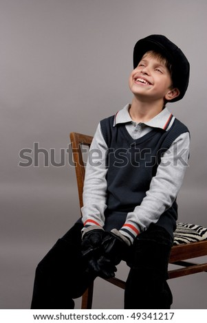 teenager caucasian boy in modern fashion cap sitting with pretty smile in gloves isolated