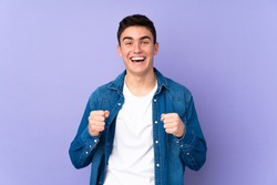 Teenager caucasian  handsome man isolated on purple background celebrating a victory in winner position