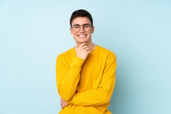 Teenager caucasian handsome man isolated on purple background with glasses and smiling