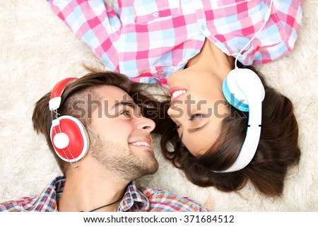 Teenager couple listening to music with headphones on a carpet