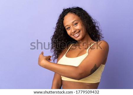 Teenager cuban girl isolated on purple background pointing back Foto stock ©