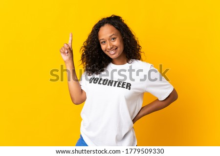 Teenager cuban volunteer girl isolated on yellow background pointing up a great idea Foto stock ©