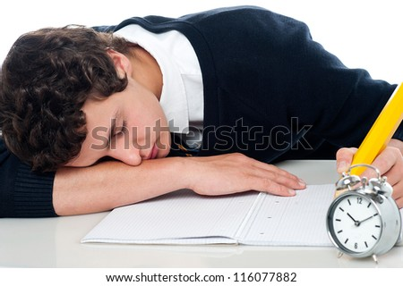 Teenager dozing off while writing his test. Fast asleep
