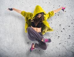 Teenager girl dancing hip hop over textured background