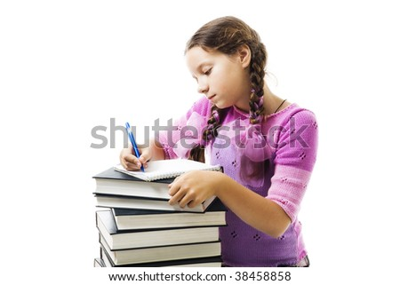 Teenager girl do homework,writing in textbook, on pile of books with concentration look,isolated on white