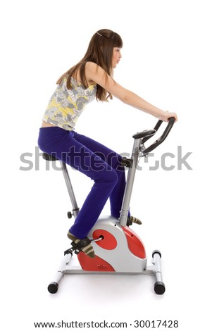 Teenager girl doing fitness on a stationary bike isolated on white