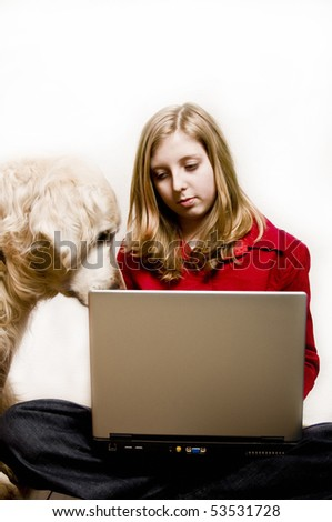 teenager girl doing her homework on a laptop with her dog beside