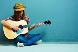 Teenager girl guitar play sitting on a floor. Blue background. Country style.